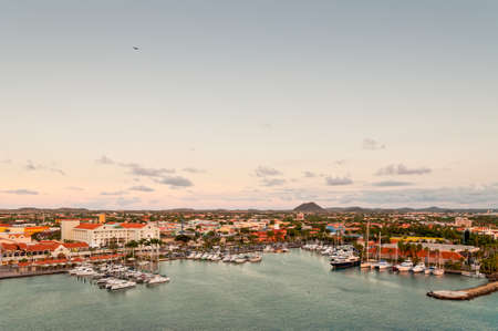 nautical structure: Oranjestad, Aruba - December 1, 2011: A view of the main harbor on Aruba looking inland in the evening. This photo, from a cruise ship, looks down over the city and boats. Dutch province named Oranjestad, Aruba - beautiful Caribbean Island. Editorial