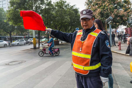 Xian, China - October 17, 2013: Chinese Traffic Warden is working at intersection in Xian, Shaanxi Province, China.