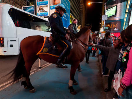 times square new york: New York, USA - November 20, 2011: Two Police Officers riding horses at Broadway in Times Square, New York City, USA. People walking towards police horses and talk to officer.