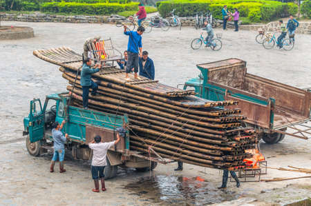 unload: Yangshuo, China - October 20, 2013: Chinese workers unload bamboo rafts on the banks of the Li river, Yangshuo, China. Editorial