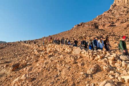 monte sinai: Monte Sinaí, Egipto - 25 de noviembre de 2010: Los peregrinos descienden del Monte Sinaí después de reunirse con el amanecer y beduinos con los camellos ayudar a las personas a 25 de noviembre de 2010. Cada día cientos de turistas recibidos la salida del sol en el Monte Sinaí. La creencia de todos los pecados Will B