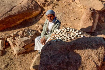 monte sinai: Sinaí, Egipto - 25 de noviembre de 2010: beduina chico cerca del Monte Sinaí, que vende piedras locales como recuerdos de rutas de peregrinos y otros turistas el 25 de Noviembre, 2010