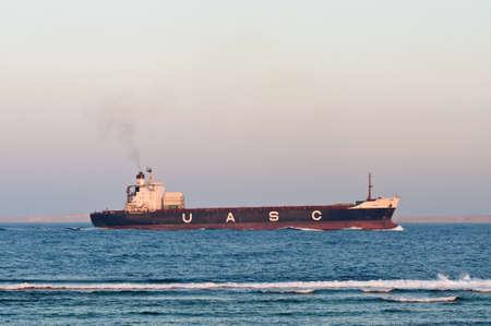 bandera de egipto: Sharm El Sheikh, Egypt - November 21, 2010: Container ship Hammurabi (almost empty) sails along the shore of the Red Sea near Sharm El Sheikh, Egypt at November 21, 2010. Type of vessel: Container Ship. Flag: Kuwait.