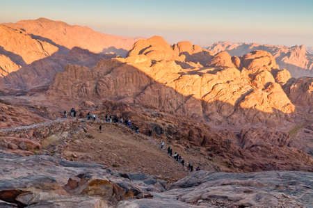 sinai desert: Mount Sinai, Egypt - November 25, 2010: Pilgrims and tourists on the pathway from the Mount Sinai peak and panorama rocks of Mount Sinai in early morning at November 25, 2010. According to the Book of Exodus, Mount Sinai is the mountain at which the Ten C