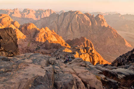 Mount Sinai, Egypt - November 25, 2010: Pilgrims and tourists on the pathway from the Mount Sinai peak and panorama rocks of Mount Sinai in early morning.
