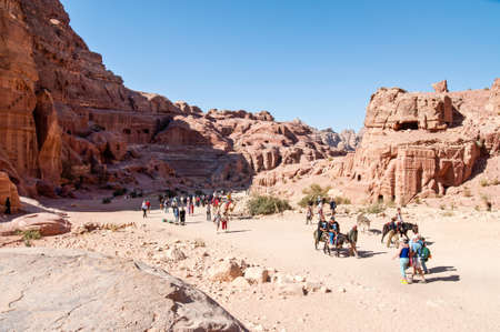 Petra, Jordan - November 20, 2010: Tourists visiting the ancient ruins of Petra on foot, donkeys, horses and camels. The spectacular road that goes to Petra is more than a kilometer long.