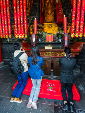 jade buddha temple: Shanghai, China - October 26, 2013: Chinese believers praying in the Jade Buddha Temple in Shanghai, China. Buddhism is enjoying a revival in modern liberal China.