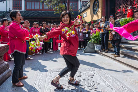 Shanghai, China - October 26, 2013: Chinese woman dancing with flowers near the Jade Buddha Temple in Shanghai, China. Buddhism is enjoying a revival in modern liberal China.