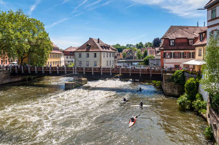 Bamberg, Germany - May 22, 2016: Tourists on a bridge and canoe slalom on the River Regnitz, Bamberg, Bavaria, Germany, Europe. The historic city center is a listed UNESCO world heritage site.