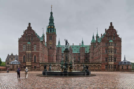 Hillerod, Denmark - August 06, 2010: Tourists visiting the Frederiksborg palace and the baroque gardens in rainy weather. The palace dates back to the 16th century, and now houses The Museum of National History in Hillerod, Denmark on August 06, 2010.