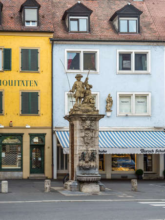 brass rod: Wurzburg, Germany - May 22, 2016: Public vintage drinking fountain (water tap) with young fishermen statue on the street of the old town of Wurzburg, Lower Franconia, Bavaria, Germany.