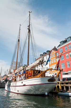 townhouses: Copenhagen, Denmark - August 5, 2010: Old sailing boat in Nyhavn. Nyhavn is a historic waterfront. It is lined by colorful 17th and 18th century townhouses and bars, cafes and restaurants. In its function as a heritage harbor, the canal has many histori