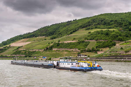 Trechtingshausen, Germany - May 23, 2016: Tanker barge (tankgas) Thera on the Rhine River near Trechtingshausen in cloudy weather, Rhine Valley, UNESCO World Heritage Site, Rhineland-Palatinate, Germany.