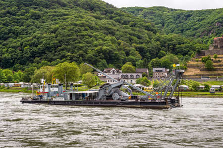 Trechtingshausen, Germany - May 23, 2016: Service vessel Carl Straat on the Rhine River near Trechtingshausen in cloudy weather, Rhine Valley, UNESCO World Heritage Site, Rhineland-Palatinate, Germany. Service vessel Carl Straat has a diving bell allowing