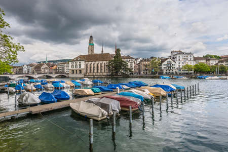 wideangle: Zurich, Switzerland - May 24, 2016: A wide-angle view across the Limmat river to the Zurich Downtown in overcast rainy weather, Switzerland. Boats in the foreground.