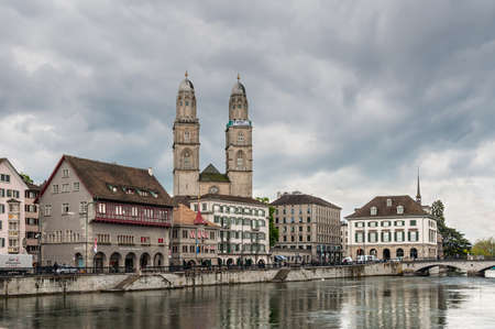 Zurich, Switzerland - May 24, 2016: View of the Grossmunster church (Great Minster), various houses and Limmat river in Zurich in overcast rainy weather, Switzerland. Editorial