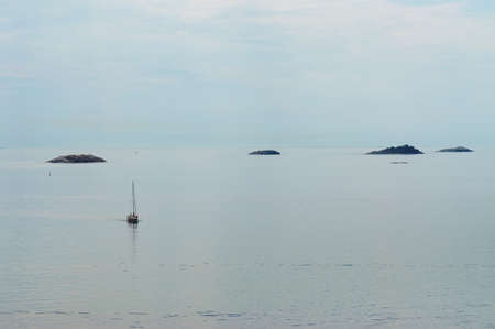 Lonely yacht and islands in the sea in a minimalist style Stok Fotoğraf