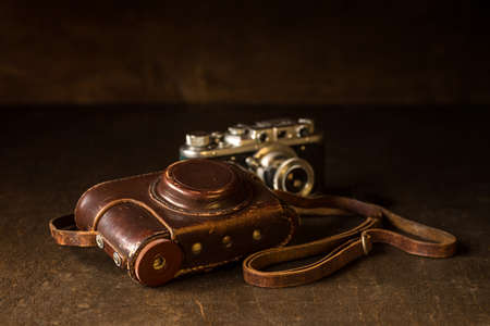 Still life with old leather cover and photo camera. Old rangefinder 35mm camera from WWII era. Stock Photo