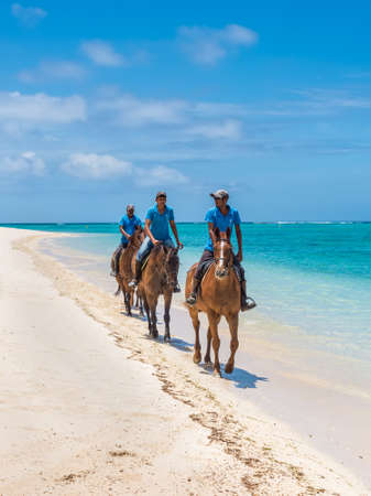 Le Morne, Mauritius - December 7, 2015: Men ride horses on the Le Morne Beach, one of the finest beaches in Mauritius and the site of many tourism facilities.