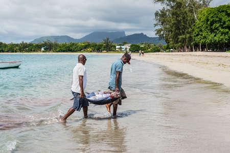 fish vendor: Tamarin, Mauritius - December 9, 2015: Fishermen carry two tuna on the beach of Tamarin Bay in Mauritius. Editorial
