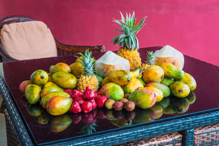 Fresh tropical Mauritius fruits on a purple glass table in the magenta background. The selection includes Coconut, Rose Apple, Mango and Pineapples.