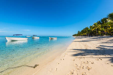 Le Morne, Mauritius - December 11, 2015: A sunny day with boats on the Le Morne Beach, one of the finest beaches in Mauritius and the site of many tourism facilities.
