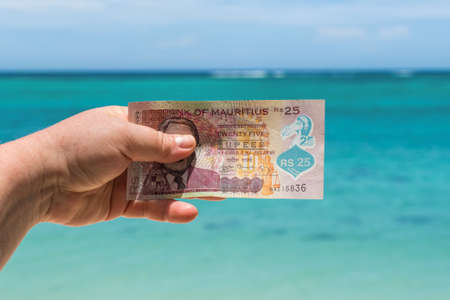 Hand holding bill against the sea - 25 Mauritian rupees bank note with traditional Dodo bird depicted on it