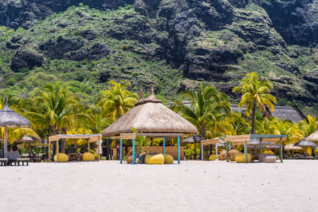 seating area: Le Morne, Mauritius - December 11, 2015: People are relaxing on the tropical Le Morne beach with coconut palms, one of the finest beaches in Mauritius. Le Morne Brabant mountain in the background.