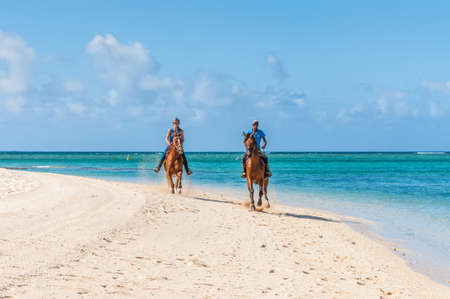 Le Morne, Mauritius - December 11, 2015: Couple riding on horseback along the sea on the Le Morne Beach, one of the finest beaches in Mauritius and the site of many tourism facilities.