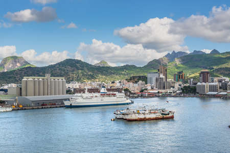 Port Louis, Mauritius - December 12, 2015: Port Louis cityscape, Mauritius. Ships in the harbor in the foreground. The city is the countrys economic, cultural, political centre and most populous city.