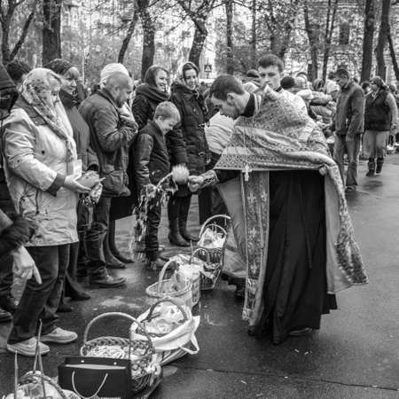 Kyiv, Ukraine - April 16, 2017:  Priest blessing the happy people during Holy Easter Sunday ceremony outside St Volodymyrs Cathedral in Kyiv, Ukraine. Black and white photography. Editorial