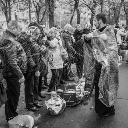 glorify: Kyiv, Ukraine - April 16, 2017:  Priest blessing the happy people during Holy Easter Sunday ceremony outside St Volodymyrs Cathedral in Kyiv, Ukraine. Black and white photography. Editorial
