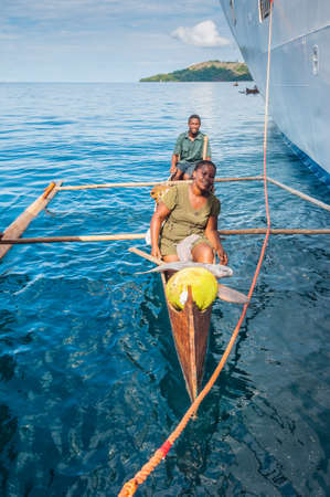 Hell-Ville, Madagascar - December 19, 2015: Malagasy vendors from their outrigger canoe offer fish and tropical fruits to ship passengers at Hell-Ville, Nosy Be Island, Madagascar.