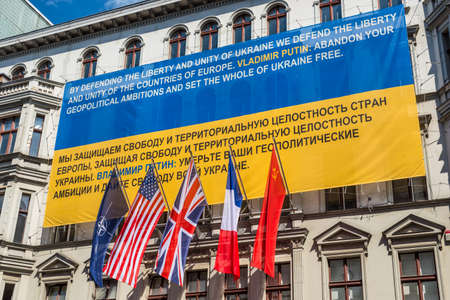 am: Berlin, Germany - May 28, 2017: Flags of Ukraine, NATO, USA, Great Britain, France, former USSR on the wall of the Haus am Checkpoint Charlie museum as solidarity with Ukraine in Berlin, Germany. Banner against Russian aggression in Ukraine.
