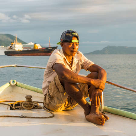 boatman: Hell-Ville, Madagascar - December 19, 2015: Malagasy boatman sailing in the rays of the setting sun on the boat in Andavakotakona Bay, near Hell-Ville, Nosy Be Island, Madagascar.