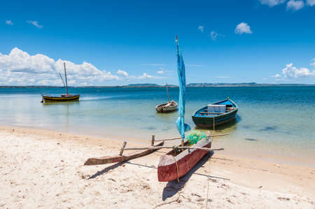 resourceful: Malagasy outrigger pirogue with sail and boats on the white beach, Madagascar