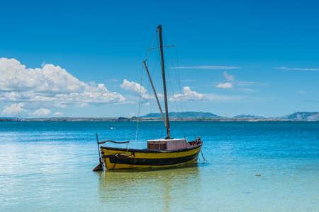 Sail boat on the sea coast.