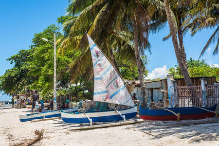 genre: Ramena, Madagascar - December 20, 2015: Local villagers and traditional malagasy wooden sail boat piroga in Ramena, Madagascar. Ramena is a charming, steadily growing fishing village located in Diego Suarez Bay.