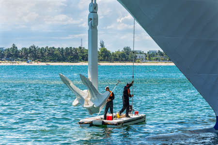 cleaning crew: Toamasina, Madagascar - December 22, 2017: Two workers clean and make maintenance service to the anchor of a passenger ship moored at Toamasina, Madagascar, East Africa. Editorial