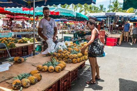 Saint-Paul, Reunion Island, France - December 24, 2015: Vendor fresh fruit pineapple on a local market in Saint Paul on the island of La Reunion (France) in the Indian ocean. Editorial