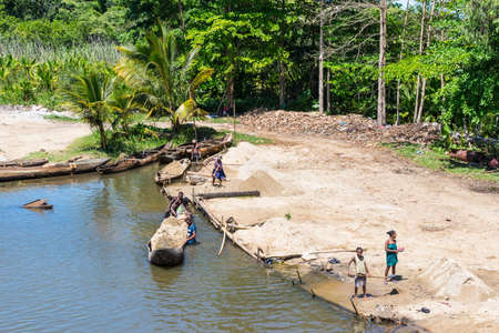 Ivoloina, Madagascar - December 22, 2015: Malagasy countryside people from the village unload sand from traditional handmade dugout wooden boats near the city of Toamasina (Tamatave), Madagascar, East Africa. Everyday life on the river.