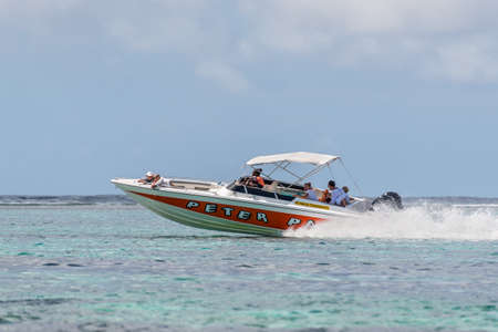le: Blue Bay, Mauritius - December 27, 2015: Luxury private speed boat sails with tourists on the Blue Bay Beach, one of the finest beaches in Mauritius and the site of many tourism facilities. Editorial