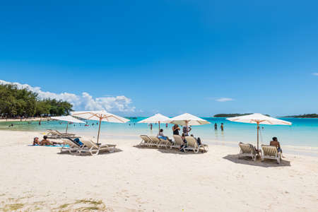 Blue Bay, Mauritius - December 27, 2015: People relax under umbrellas and in the sun on the tropical Blue Bay beach, Mauritius Island. Idyllic travel background. Editorial