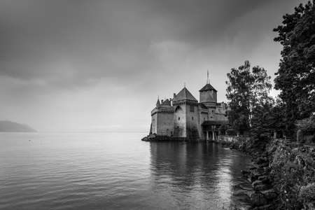 Montreux, Switzerland - May 25, 2016: View of famous Chateau de Chillon at Lake Geneva  in cloudy weather, one of Switzerlands major tourist attractions. Black and white photography.