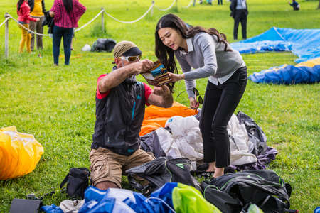 Interlaken, Switzerland - May 26, 2016: Paragliding instructor shows the girl the advertising of paragliding in Interlaken, Switzerland.