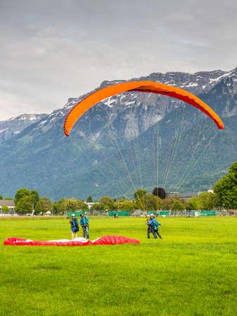Interlaken, Switzerland - May 26, 2016: Tandem paraglider after landing against the background of the Swiss Alps in Interlaken, Switzerland.