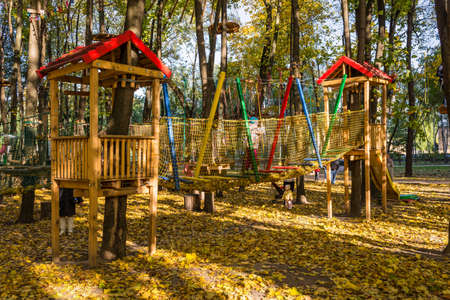 Kyiv, Ukraine - October 16, 2017: Children with parents are passing the route in the climbing adventure rope park a warm autumn day in Kyiv city, Ukraine. Selective focus.
