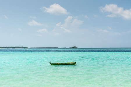 Small boat and bungalow on the horizon on Maldives - nature travel background - exotic beautiful marine beach of Gulhi island