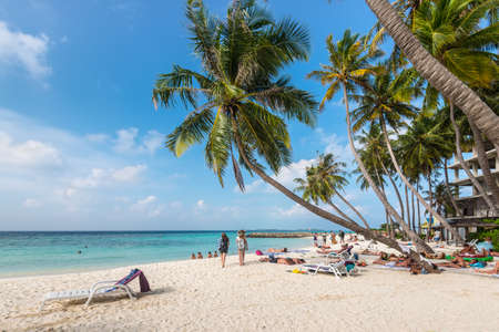 Maafushi Island, Maldives - November 17, 2017: People enjoying sunny day in a tropical beach of the Maafushi Island in Maldives, Indian Ocean.