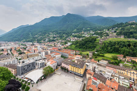 Bellinzona, Switzerland - May 28, 2016: Bellinzona cityscape view from castle under cloudy sky in Switzerland, surrounding with high Alps mountains. Editorial